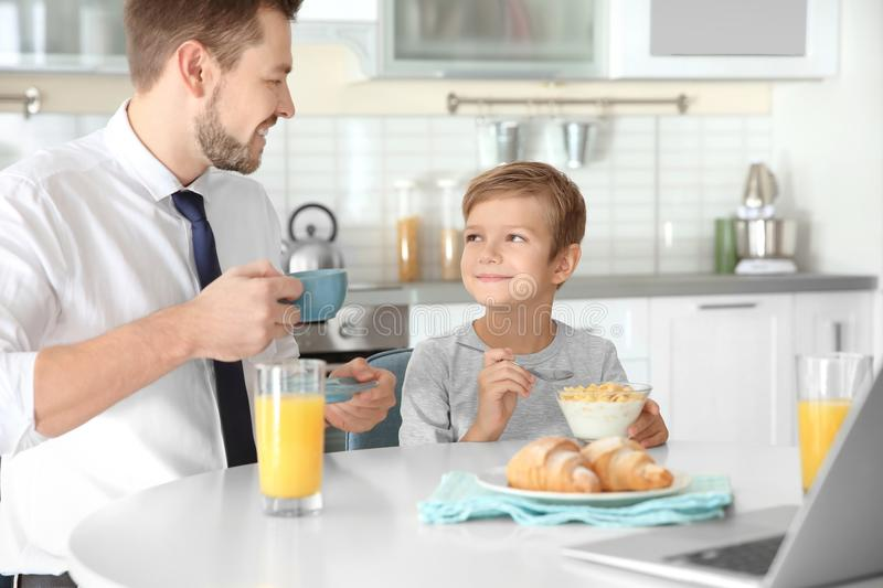 Father with son having breakfast stock image