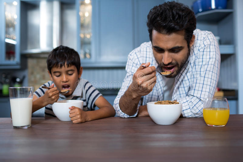 Father and son having breakfast. At home stock images