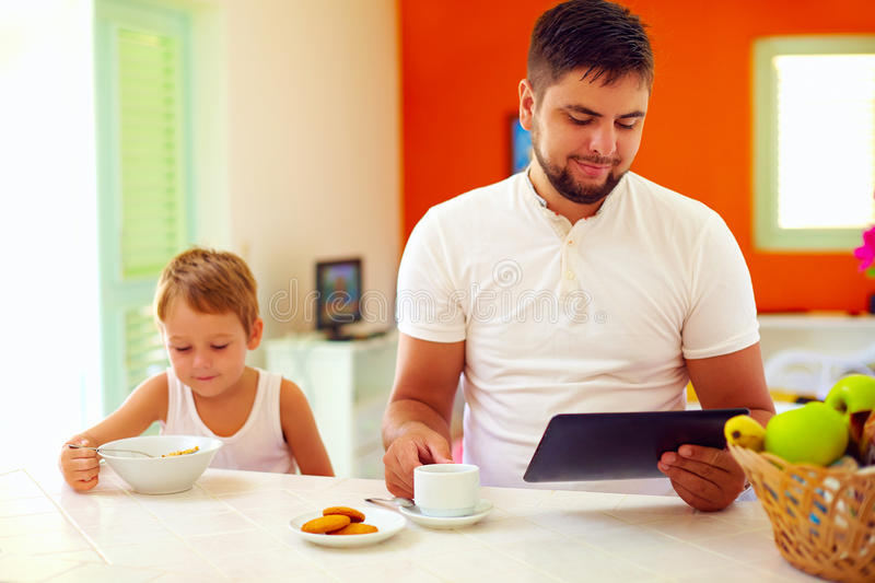 Father and son having breakfast in the morning at home kitchen stock images
