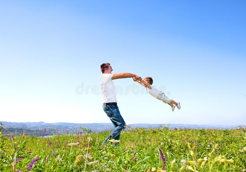 Father and son having fun on madow stock photos