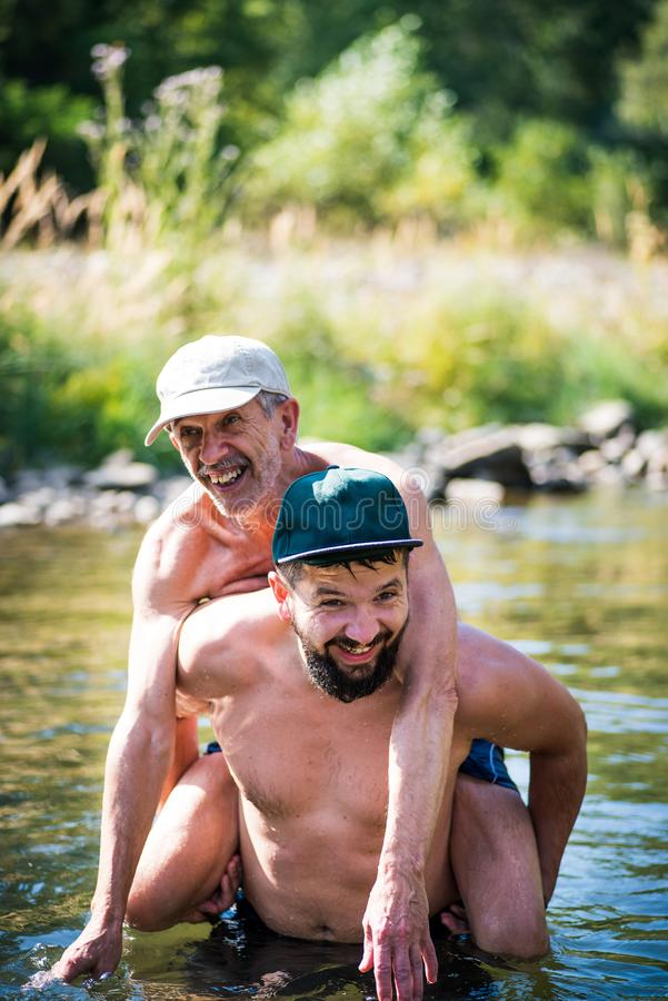 Father and son having fun in the river water stock photo