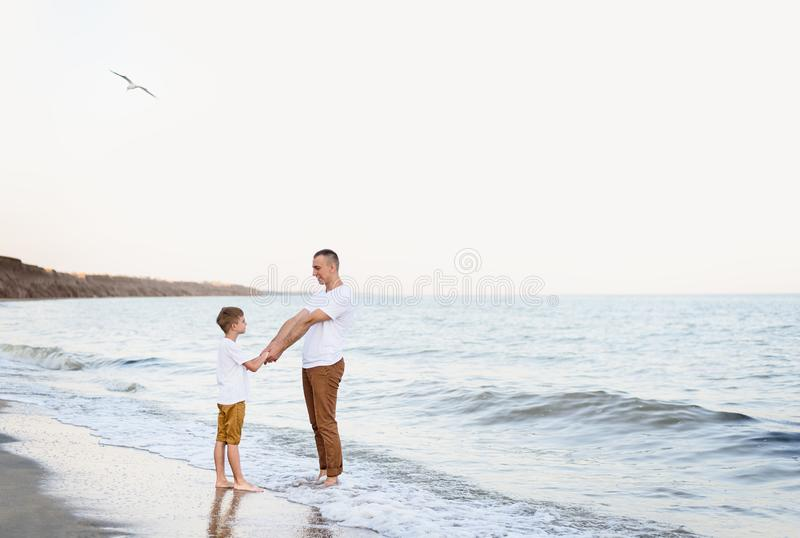 Father and son having fun on the sea coast. Family vacation. Friendship stock photography