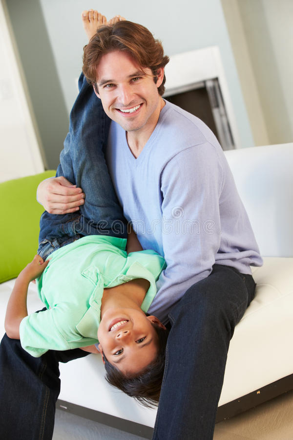 Father And Son Having Fun On Sofa Together royalty free stock image