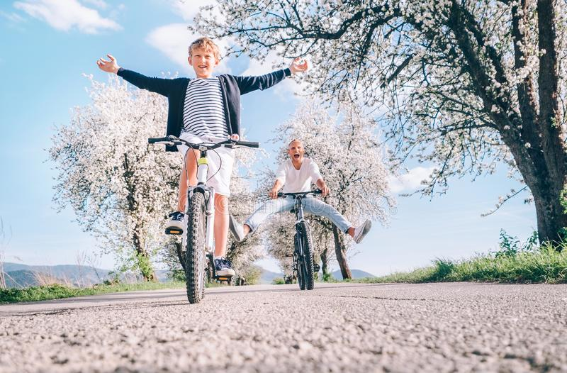 Father and son having fun when riding bicycles on country road under blossom trees. Healthy sporty lifestyle concept image. Father and son having fun spreading stock photo