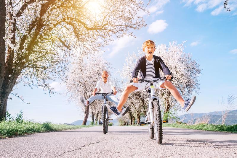 Father and son having fun when riding bicycles on country road under blossom trees. Healthy sporty lifestyle concept image. Father and son having fun spreading royalty free stock photo