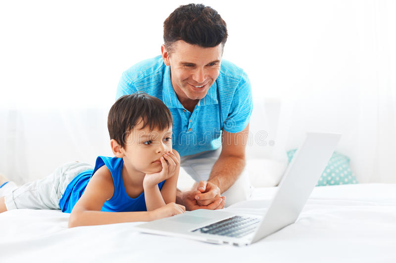 Father and son having fun using laptop stock photo