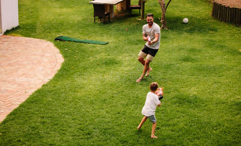 Father and son having fun with water guns outdoors stock images