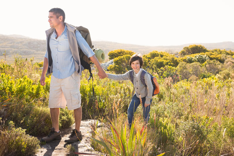 Father and son hiking through mountains stock photography
