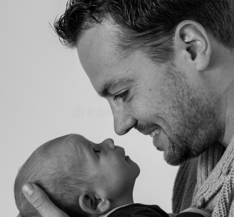 Father and son. Father and his 1 month old son are making eye contact stock photo