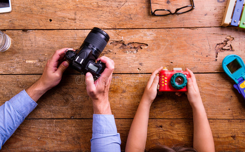 Father and son holding cameras, old wooden office desk. Hands of unrecognizable father and son holding cameras, old office desk. Studio shot on wooden background stock photo