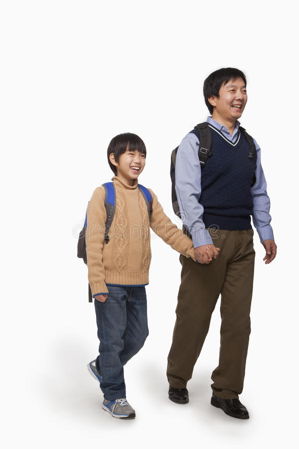 Father and son holding hands and walking, studio shot stock images
