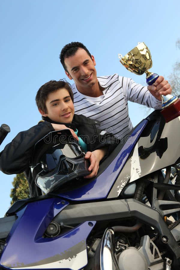 Father and son holding trophy. Father and son holding a trophy royalty free stock photo