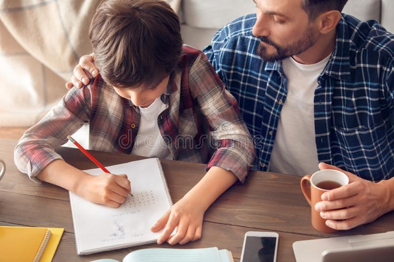 Father and son at home sitting at table dad drinking tea touching shoulder supportive of boy doing exercise. Father and little son together at home sitting at royalty free stock photos