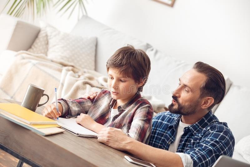 Father and son at home sitting at table dad helping boy pronouncong words. Father and little son together at home sitting at table dad helping boy writing stock photos