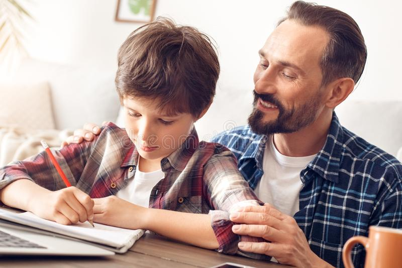 Father and son at home sitting at table dad smiling watching boy doing exercise concentrated close-up stock photo