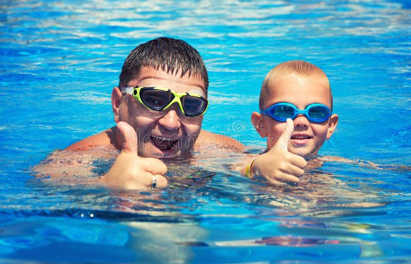 Father and son jump and swim in the pool under sun light at summer day. Leisure and swimming at holidays. stock images