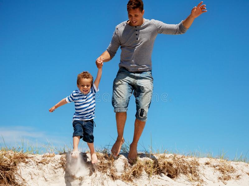 Download Father And Son Jumping Outdoors Royalty Free Stock Image - Image: 26575526