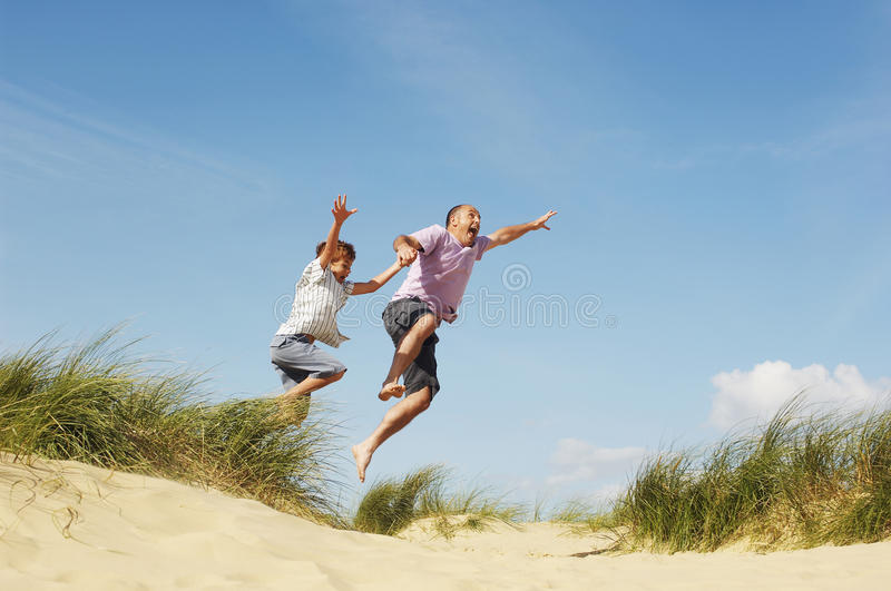 Father And Son Jumping On Sand At Beach. Cheerful father and son holding hands and jumping on sand at beach royalty free stock image