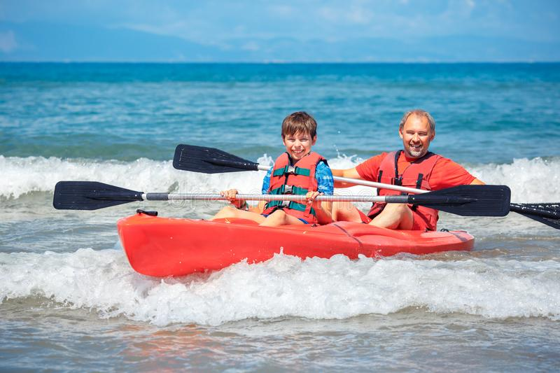 Father and son kayaking in ocean. Active vacation with young kid. Holiday activity with schoolboy child stock images