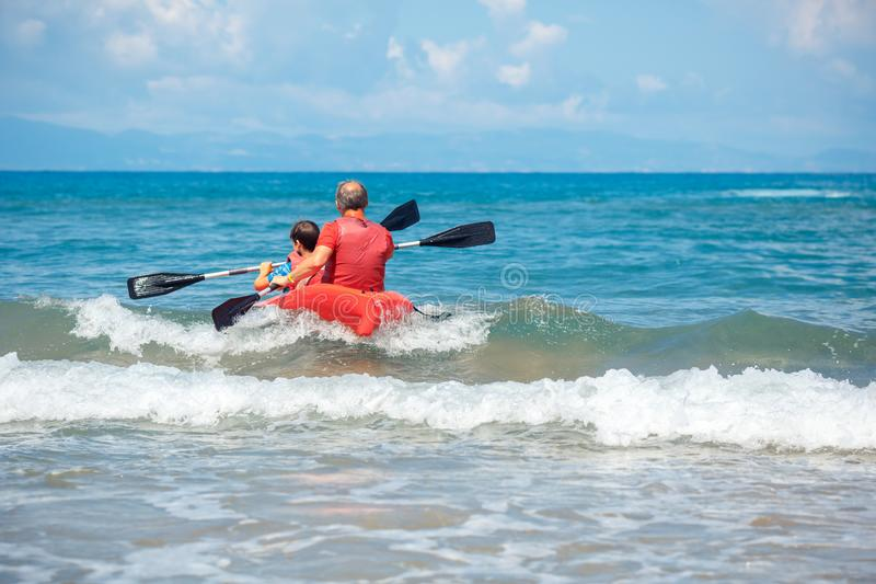 Father and son kayaking in ocean. Active vacation with young kid. Holiday activity with schoolboy child stock photo