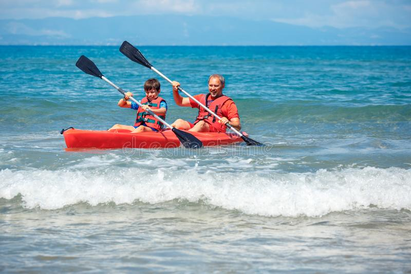 Father and son kayaking in ocean. Active vacation with young kid. Holiday activity with schoolboy child royalty free stock photography