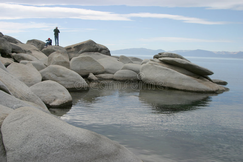 Father and Son at the Lake. A father and son enjoy climbing on the rocks at the edge of a beautifull mountain lake royalty free stock photography