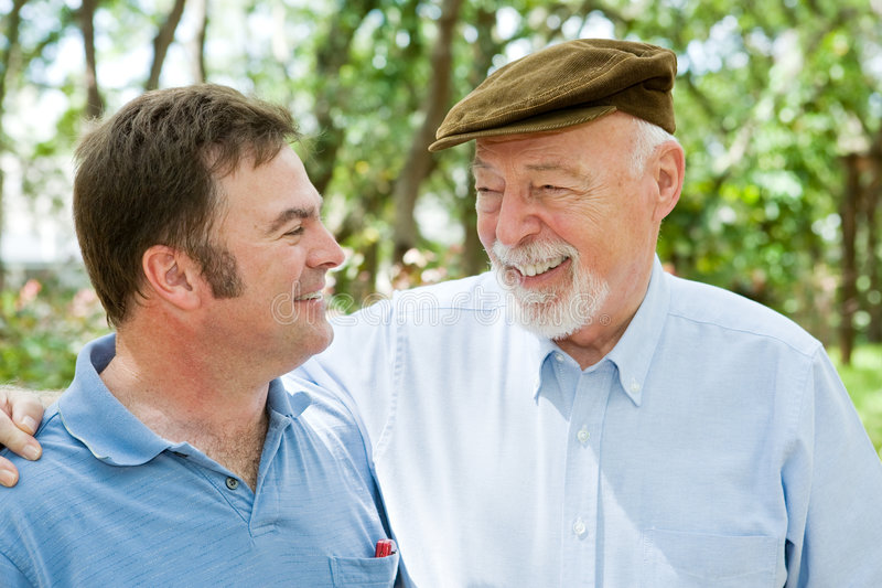 Father & Son Laughter. Senior father and adult son laughing together in the park
