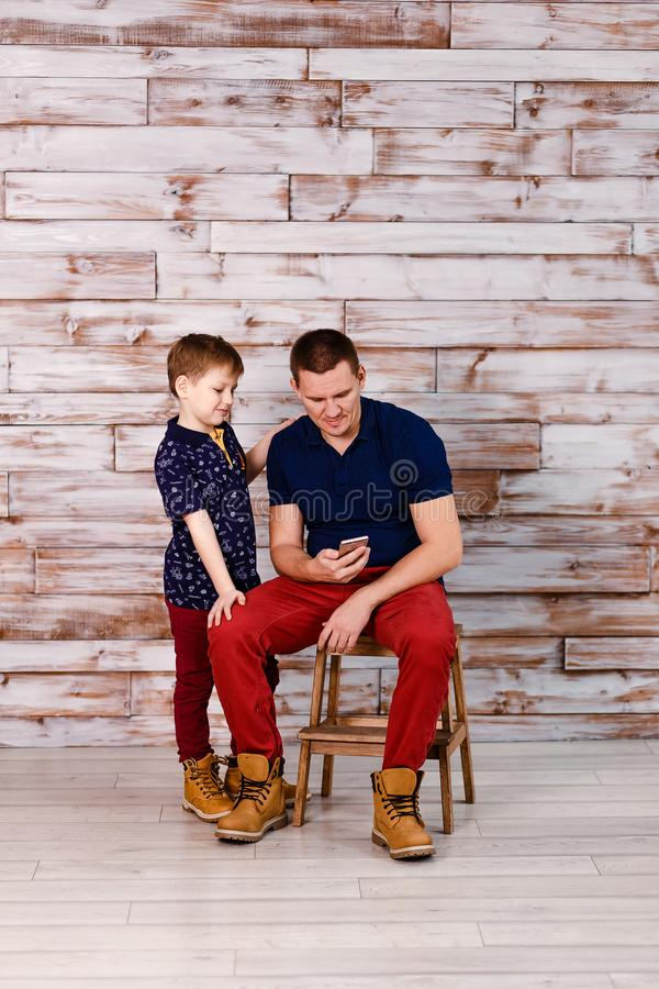 Father and son look at smartphone royalty free stock photo