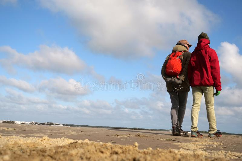 Father and son looking on the water at beautiful weather while standing on the beach which is covered with foam hills at low tide. At stormy weather the waves of royalty free stock images
