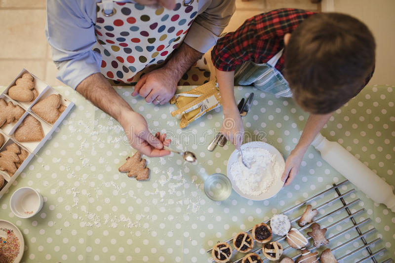 Father And Son Making Christmas Treats royalty free stock photos