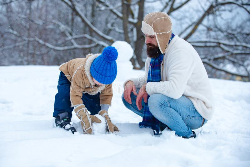 Father and son making snowman. Christmas holidays and winter new year with father and son. Winter family in frosty royalty free stock photography
