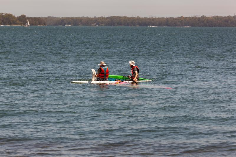 Father and son making windsurfing repairs in the water  to go faster. Bonding over a water sport competition. royalty free stock photography