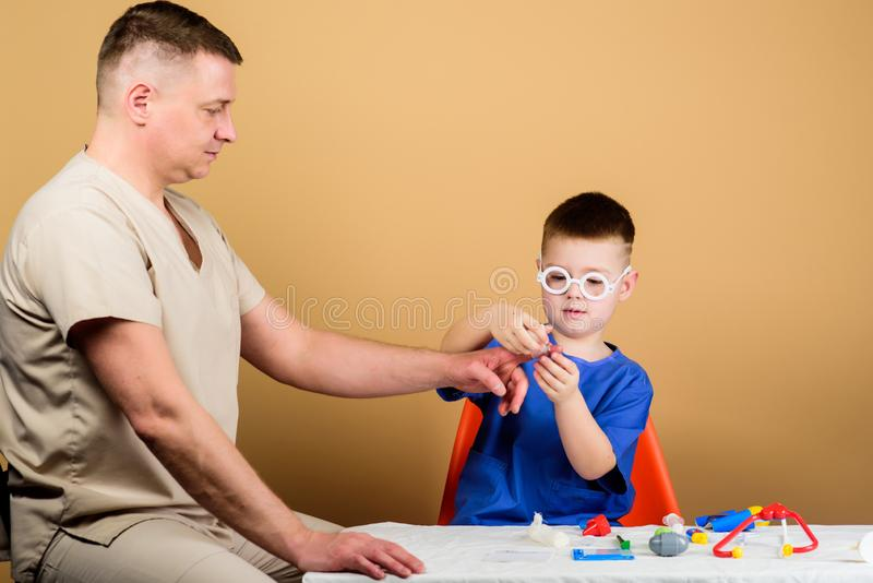 Father and son in medical uniform. family doctor. medicine and health. happy child with father with stethoscope. small royalty free stock image