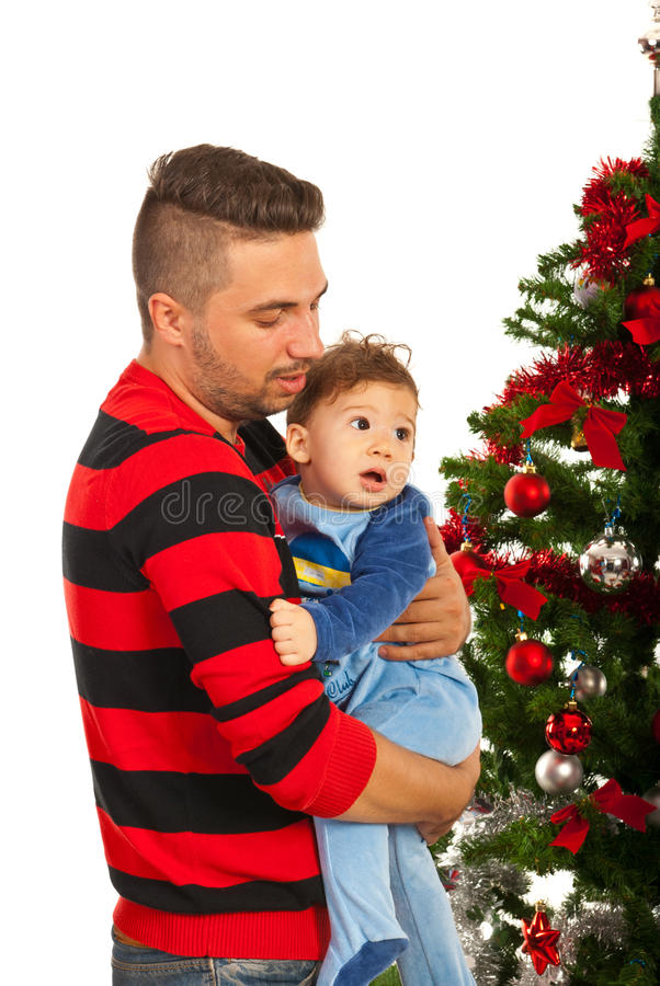 Father and son near Christmas tree. Father holding baby son and standing near Christmas tree royalty free stock images