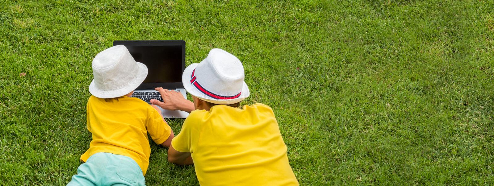Father and son with notebook on sunny summer day. New approach to education. Back view of two boys with laptop lying on royalty free stock images