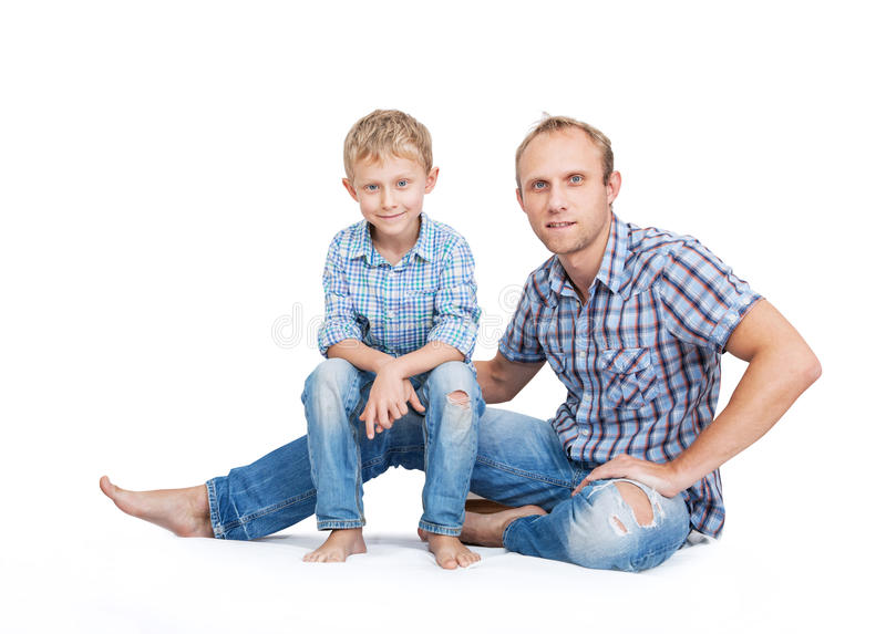 Father with son in old tattered jeans and plaid shirts on the white royalty free stock photography