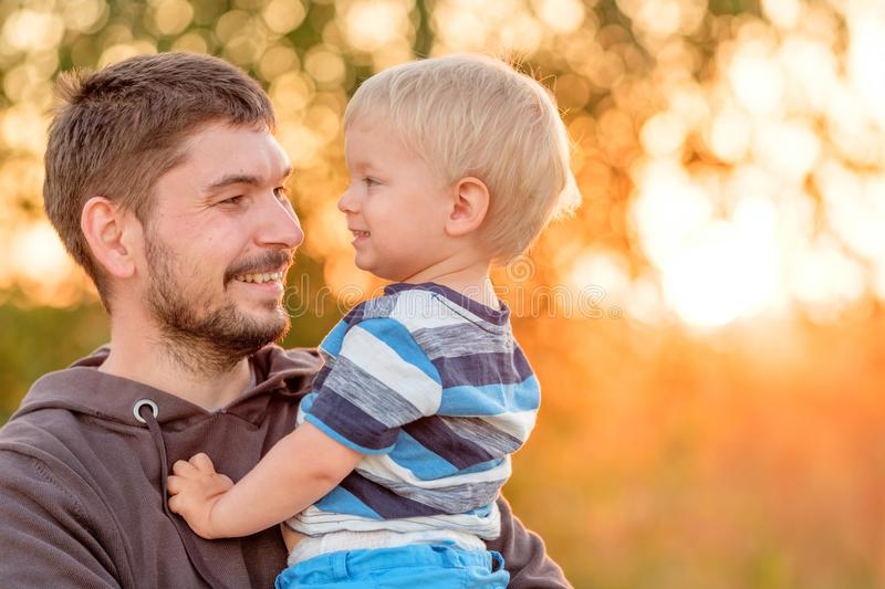 Father and son outdoor portrait in sunset sunlight. Happy men and his child having fun outdoors. Family lifestyle rural scene of father and son in sunset stock photo