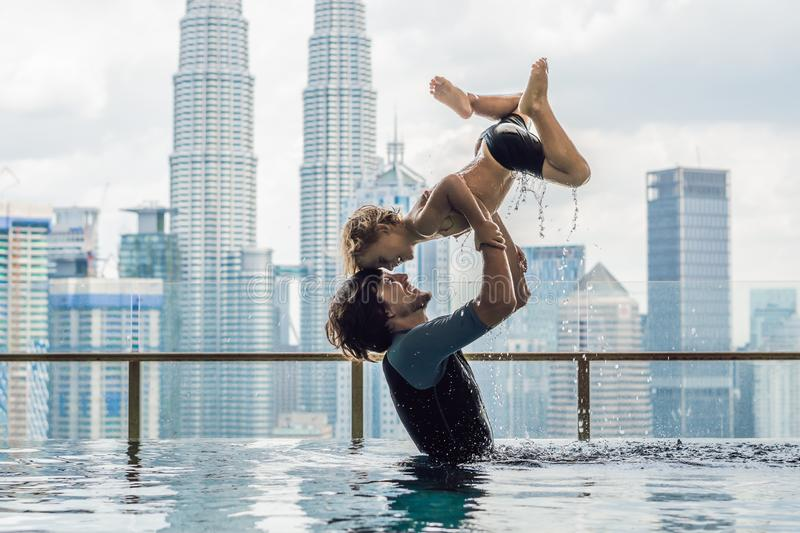 Father and son in outdoor swimming pool with city view in blue sky stock photo