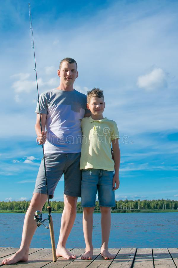 Father and son on the pier, against a beautiful landscape, holding a fishing rod for fishing royalty free stock photos