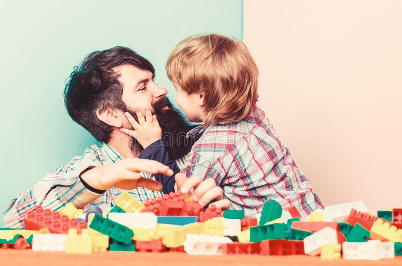 Father and son play game. building home with colorful constructor. small boy with dad playing together. child royalty free stock photo