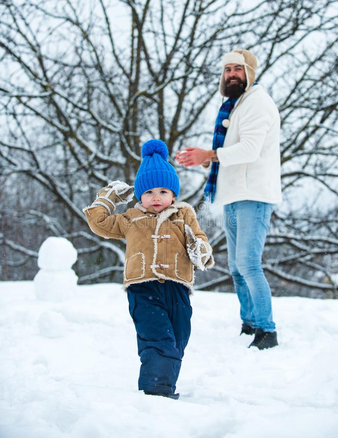 Father and son play with snowball on winter white background. Father and son playing with snow in park on white snow stock photo