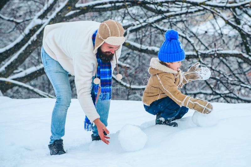 Father and son play with snowball on winter white background. Merry Christmas and Happy new year. Outdoor portrait of. Father and son in cold sunny winter stock photos