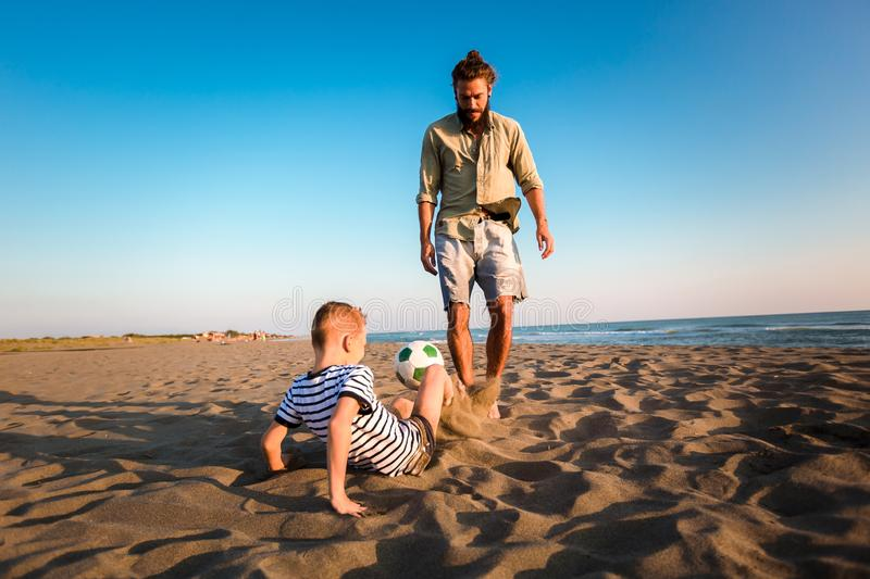 Father and son play soccer or football on the beach having great family time on summer holidays stock photo