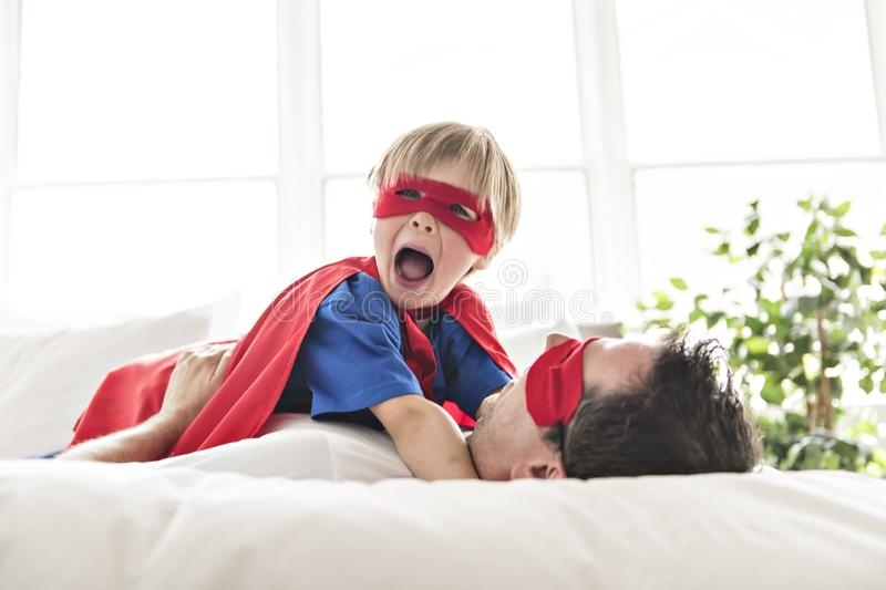 Father and son play superheroes on bed at home royalty free stock photos