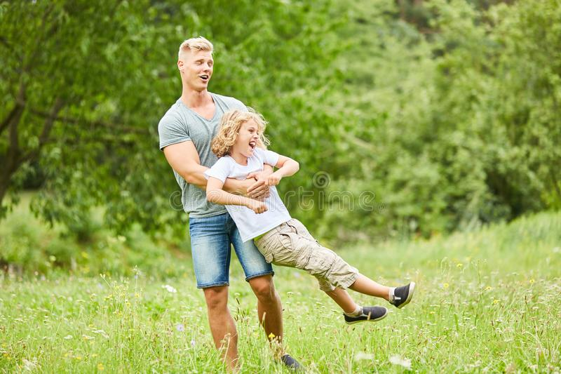 Father and son play together in the garden stock image