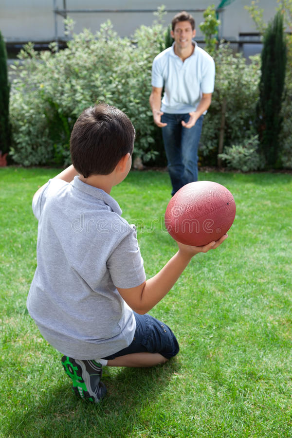 Father and son playing american football. Little kid throwing football to his father in backyard stock photo