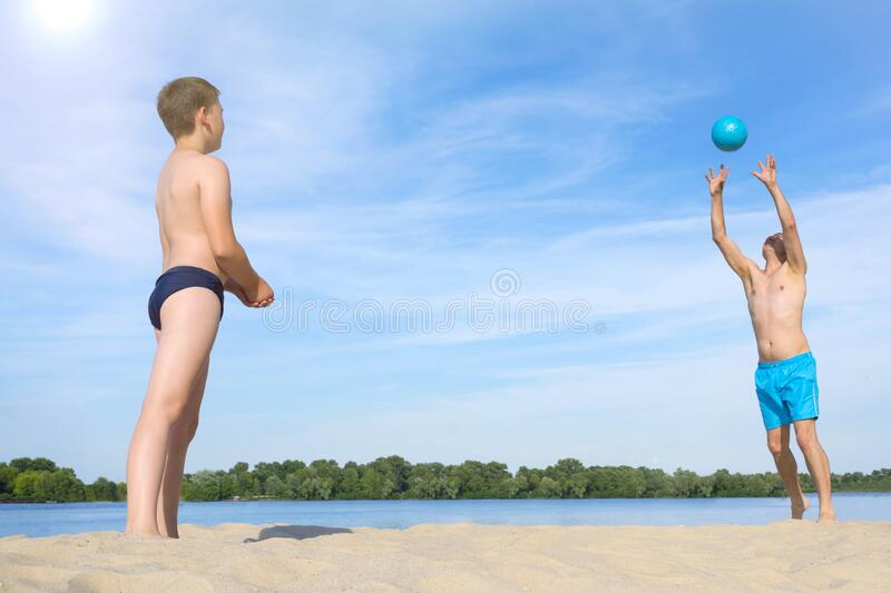 Father and son playing with the ball in the sand.  Sports games on the beach on a sunny summer day.  Sports  lifestyle.  stock images