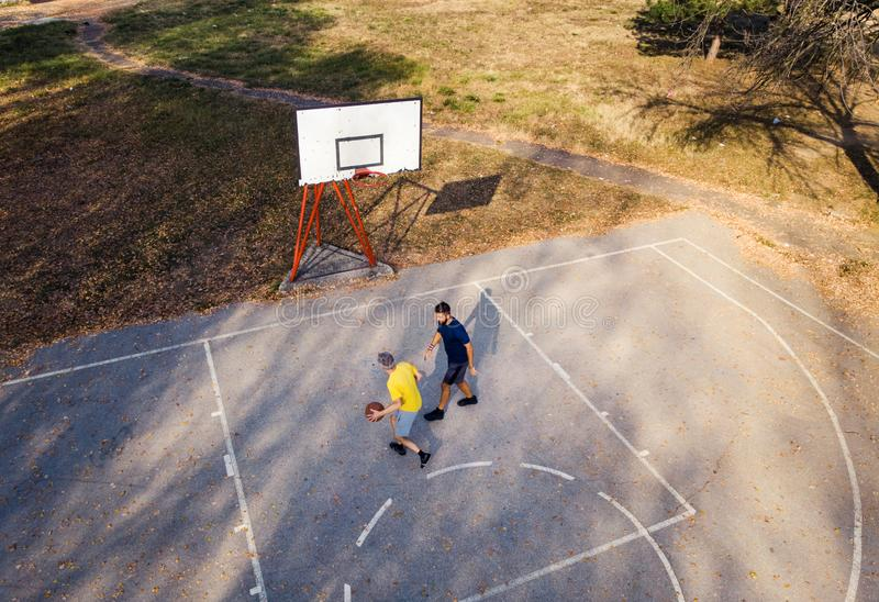 Father and son playing basketball in the park. Aerial view royalty free stock images