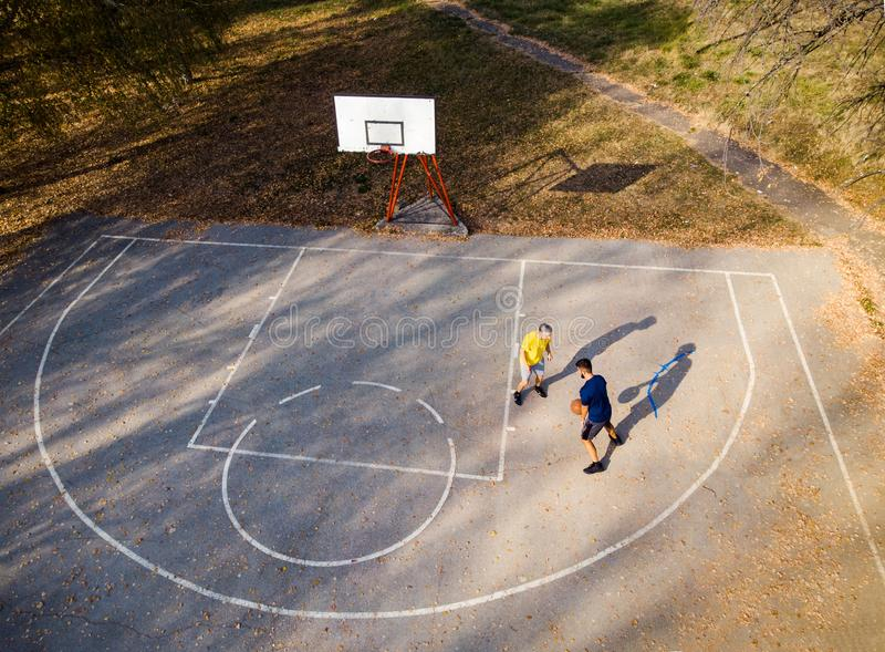 Father and son playing basketball in the park aerial. View royalty free stock photos