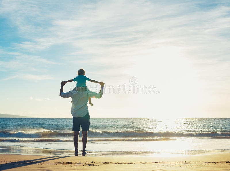 Father and Son Playing on the Beach at Sunset royalty free stock images